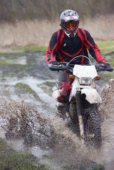 Extreme racing on mud track where young professional biker riding outdoors