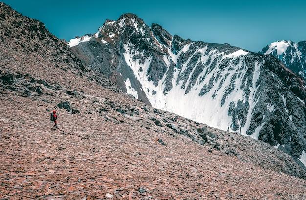 極端なレクリエーションと山岳観光。男性のハイカーが山道を下っていきます。背景には、雪をかぶった大きな山々。スペースをコピーします。