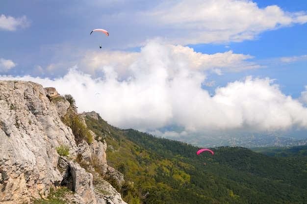 Extreme recreation, skydiver flies over the mountains and rocks. white clouds in sky