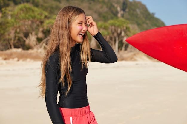エクストリームスポーツとアクティブなライフスタイルのコンセプト。黒のタートルネックのセーターと赤のショートパンツを着た、見栄えの良いスリムな女性の横向きのショット