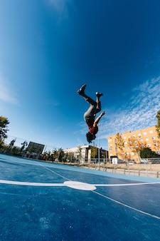 Экстремальный спорт, паркур или брейк-данс и люди концепции - молодой человек прыгает высоко