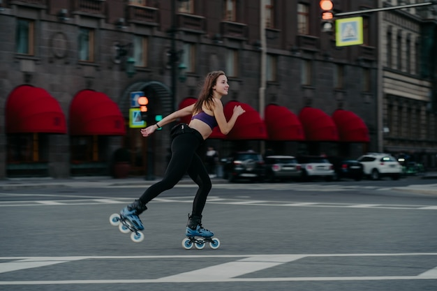 Extreme sport recreation and fitness activity concept. active woman rides on rollers in urban environment strengthens leg muscles demonstrates high level of stability balances on small wheels