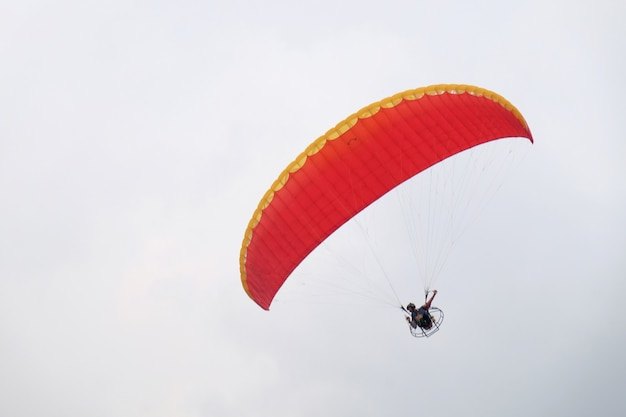 Extreme sports pilot is flying up to the cloudy sky with a paramotor engine