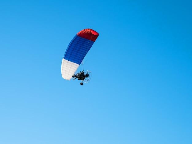 エクストリームスポーツ。青い空を背景に動力を与えられたパラシュート。