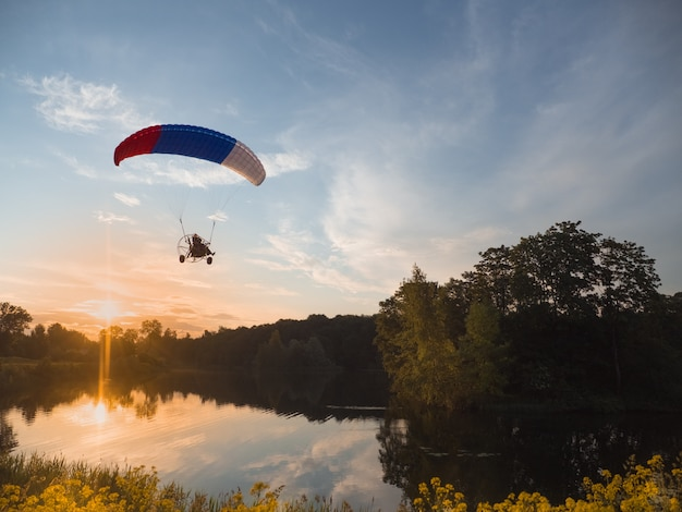Extreme sports. powered parachute in the evening against the blue sky