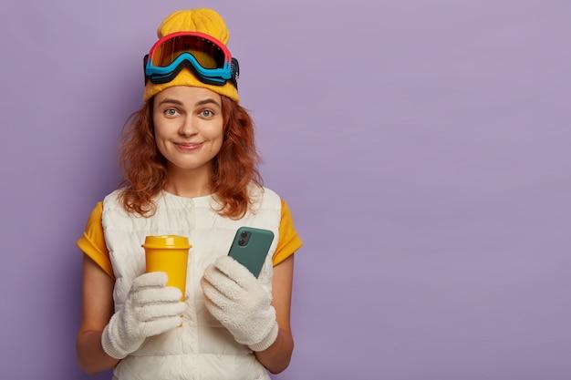 Sport invernali estremi, ricreazione e concetto di tecnologia. donna rossa felice tiene caffè da asporto e moderno telefono cellulare, essendo sciatore professionista, pubblica foto nei social network.
