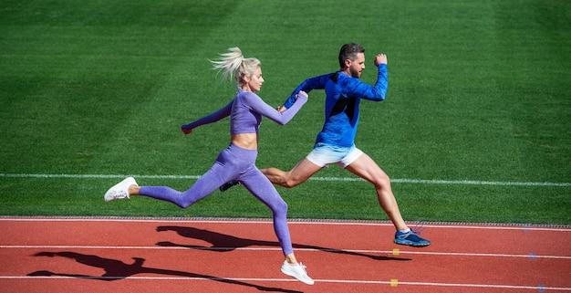 익스트림 운동. 스포츠 커플은 빨리 이기기 위해 달린다. 성공적인 피트니스 단거리 선수. 운동 남자와 섹시한 여자는 스프린트에서 경쟁합니다. 경기장 실행 트랙에 남성과 여성입니다. 건강한 생활. 마라톤 속도.