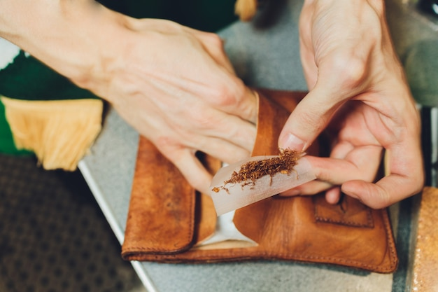 Extremely close-up view of a man hands putting a tobacco in a tobacco machine.