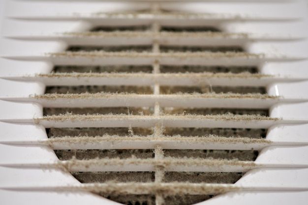 Extremely dirty air ventilation grill of hvac with dusty clogged filter, close up.