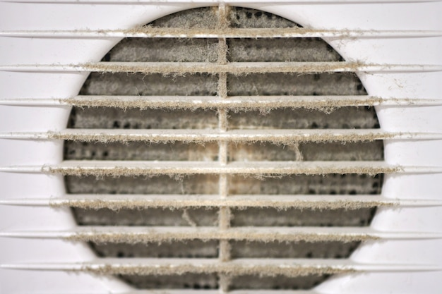 Extremely dirty air ventilation grill of hvac with dusty clogged filter, close up