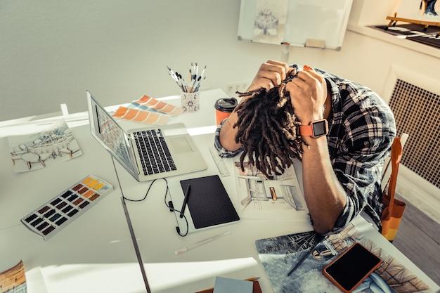 非常に疲れています。ドレッドヘアが非常に疲れていると感じている黒髪の若い有望なアーティスト
