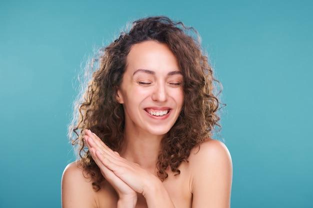 Чрезвычайно счастливая молодая женщина со здоровой кожей и красивыми темными волнистыми волосами смеется перед камерой с закрытыми глазами