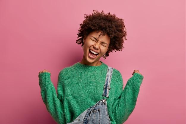 非常にうれしそうな暗い肌の女性は、くいしばられた握りこぶしを上げ、幸福から叫び、何かを勝ち取ることができて幸運だと感じ、驚くべき勝利を祝い、目を閉じて笑顔を広げ、ピンクの壁に隔離されます