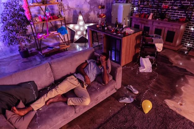 非常に痛みを伴う頭痛。極端な二日酔いのために生きることを望まずにコーチに横たわっている素足の疲れた男