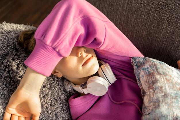 非常に晴れ。非常に晴れた日に家で寝ながら顔を閉じる 10 代の少女