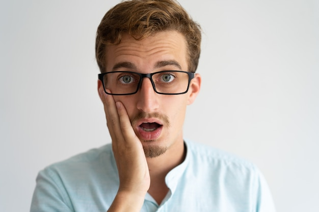 Extremely surprised office guy in glasses getting shocking news.