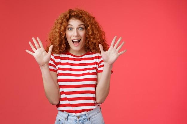 그녀는 매우 놀라운 소식을 듣고 흥분했습니다. 흥분된 감동적인 화려한 빨간 머리 여자 비명에 감탄한 놀라운 놀라움이 손을 흔들며 감동적인 입을 벌리고 매료된 빨간색 배경을 응시합니다.