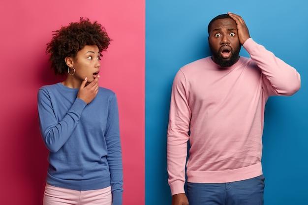 Donna e uomo etnici estremamente eccitati e stupiti, scioccati da brutte notizie improvvise, a bocca aperta, fissano con occhi spalancati