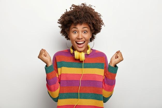 매우 행복한 아프리카 계 미국인 여성이 득점 골을 축하하고, 승리 제스처를 취하고, 주먹을 움켜 쥐고, 곱슬 머리를하고, 줄무늬가있는 화려한 점퍼를 착용하고, 일부 장치에 연결된 헤드폰을 사용합니다.