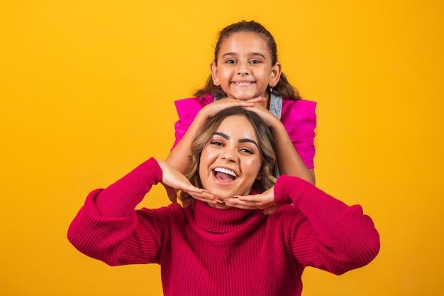 Сестры-экстраверты делают позы и выражения на желтом фоне в день брата. концепция дня брата
