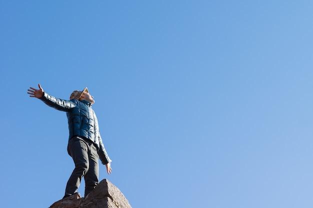 コピースペースのある澄んだ青い空を背景に、腕を広げて太陽に向かって叫んで立っている古い石の壁の上に立っているあふれんばかりの若い男、下から見上げるビュー