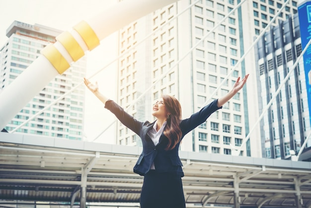 Счастливый бизнесмен exults насосных кулаков экстатический празднует успех на открытом воздухе.