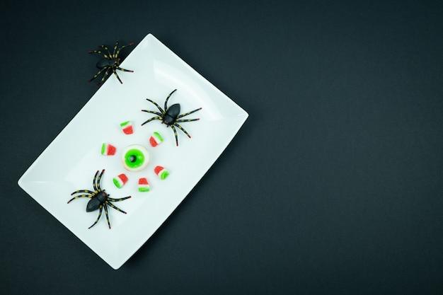 黒の背景にハロウィーンのクモと目とキャンディスイカの断片。