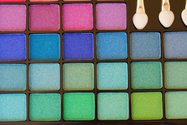 Eye brushes with colorful  eye shadows palette background
