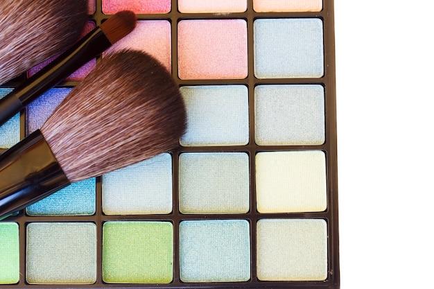 Eye brushes with colorful  eye shadows palette border on white background