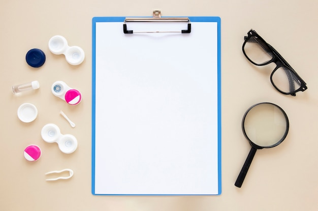 Eye care accessories on beige background with clipboard mock-up