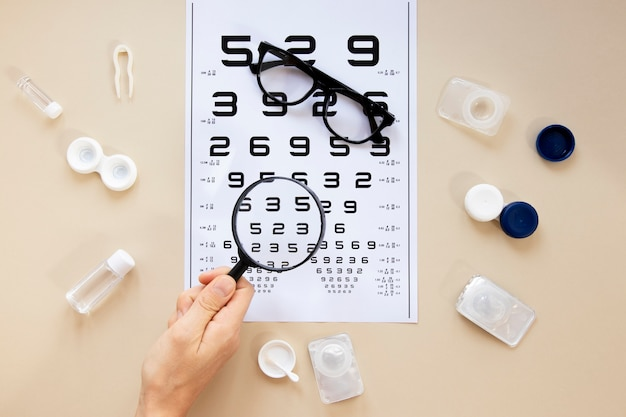 Eye care accessories on beige background with numbers table