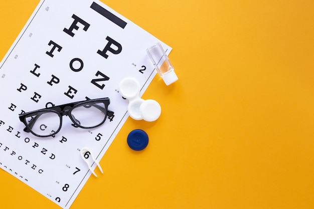 Eye care products on orange background with copy space
