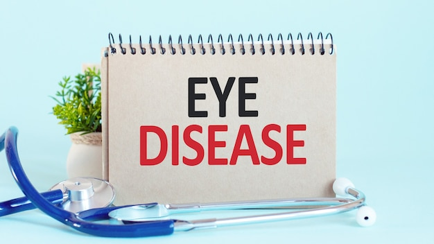 Eye disease - diagnosis written on a white piece of paper. stethoscope and green plant in a flower pot on the background. treatment and prevention of disease. medical concept. selective focus