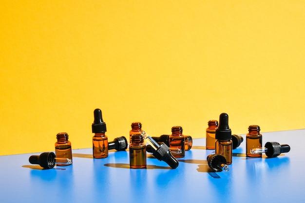 黄色と青の背景に暗い影のスポイトボトル。現代の創造的なミニマリズムの概念。コピースペース