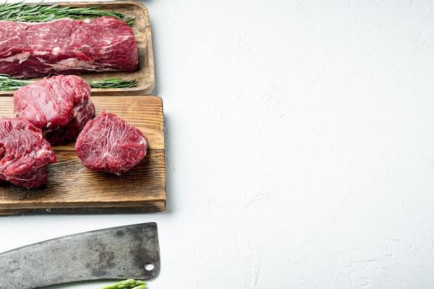 눈 필레 쇠고기 차돌박이 신선한 고기 스테이크 세트 및 흰색 돌 표면에 나무 커팅 보드에 오래된 정육점 칼