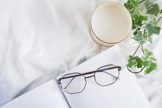 Очки для глаз, ароматическая свеча, цветок в горшке и открытый пустой блокнот на белой мятой ткани, планирование и работа дома с комфортом