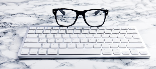 Eye glasses on a desk or office scene with keyboard
