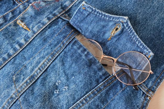 ブルーデニムジャケットのポケットにメガネ、トレンドアイメガネコピースペース