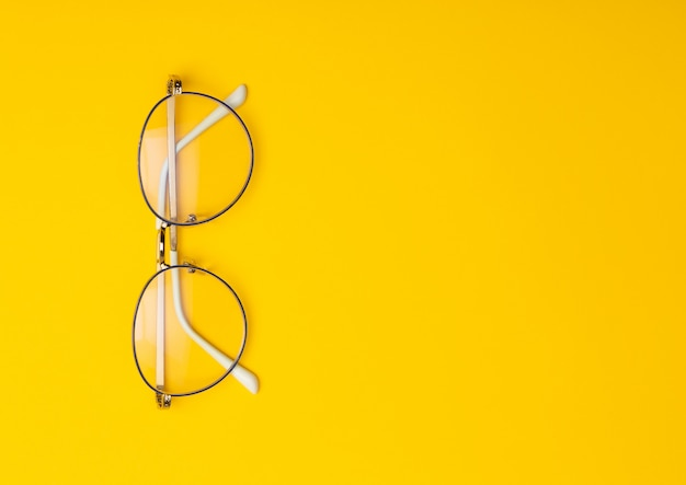Eye glasses isolated on yellow background with copyspace.