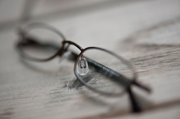 Eye glasses resting on a wooden plank