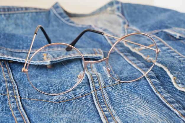 青いデニムジャケットのポケットに丸い金属フレームが付いた眼鏡、トレンドの眼鏡、レトロなスタイルのコピースペース