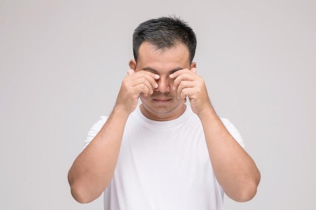 Концепция раздражения глаз: портрет азиатского мужчины в позе усталого глаза, раздражения или проблемы с его глазом.