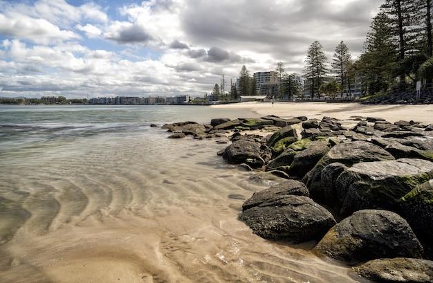 Colpo a livello degli occhi di pietre su una spiaggia vicino ad alberi ed edifici sotto il cielo nuvoloso blu