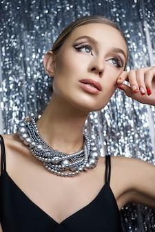 Макияж глаз блондинки на блестящей предпосылке. портрет женщины с ожерельем на шее крупным планом, идеальный макияж глаз, уход за лицом