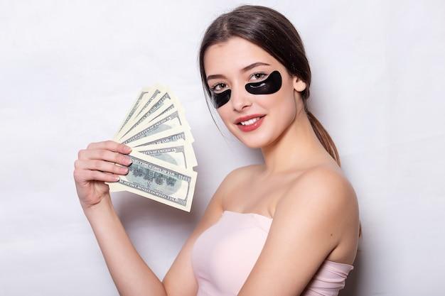 Повязка на глаз, красивая женщина с естественным макияжем и черные гидрогелевые патчи для глаз на коже лица, молодая улыбающаяся деловая женщина, держащая пачку долларов наличными деньгами в руке на белом фоне.