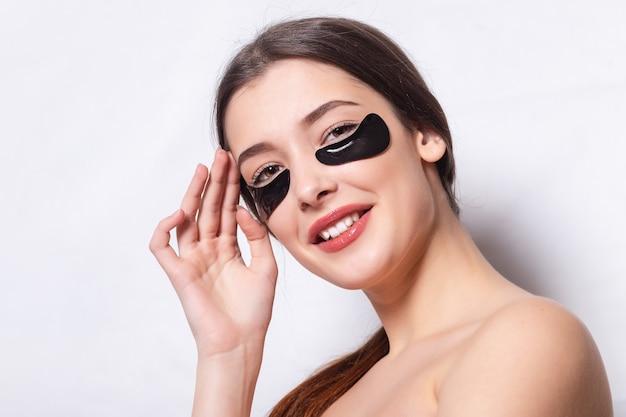 Повязка для глаз, красивая женщина с естественным макияжем и черные гидрогелевые патчи для глаз на коже лица. молодая женщина с красивой кожей накладывает черные пятна на лицо