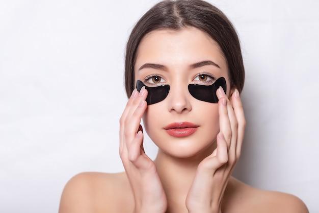 Повязка для глаз, красивая женщина с естественным макияжем и черные гидрогелевые патчи для глаз на коже лица.