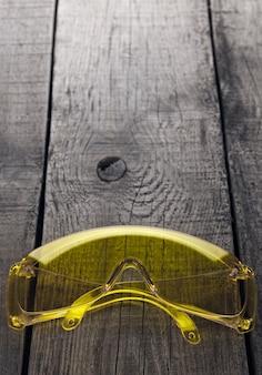 木製の背景に、修理や建設作業のための目の保護メガネ。