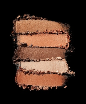 Eye shadow shimmering matte multi colored beige golden brown nude palette texture background black isolated
