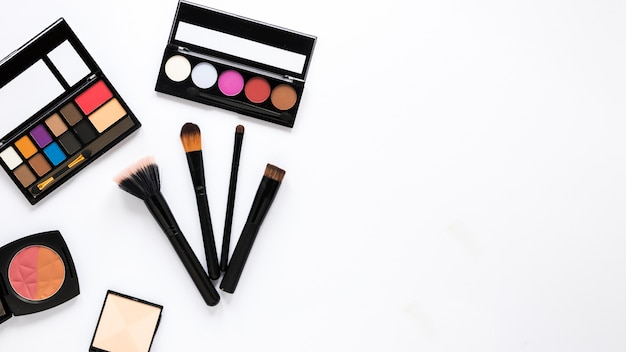 Eye shadows with brushes on white table